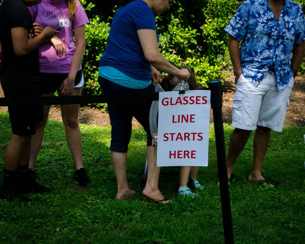 People lining up next to a sign that says Glasses Line Starts Here