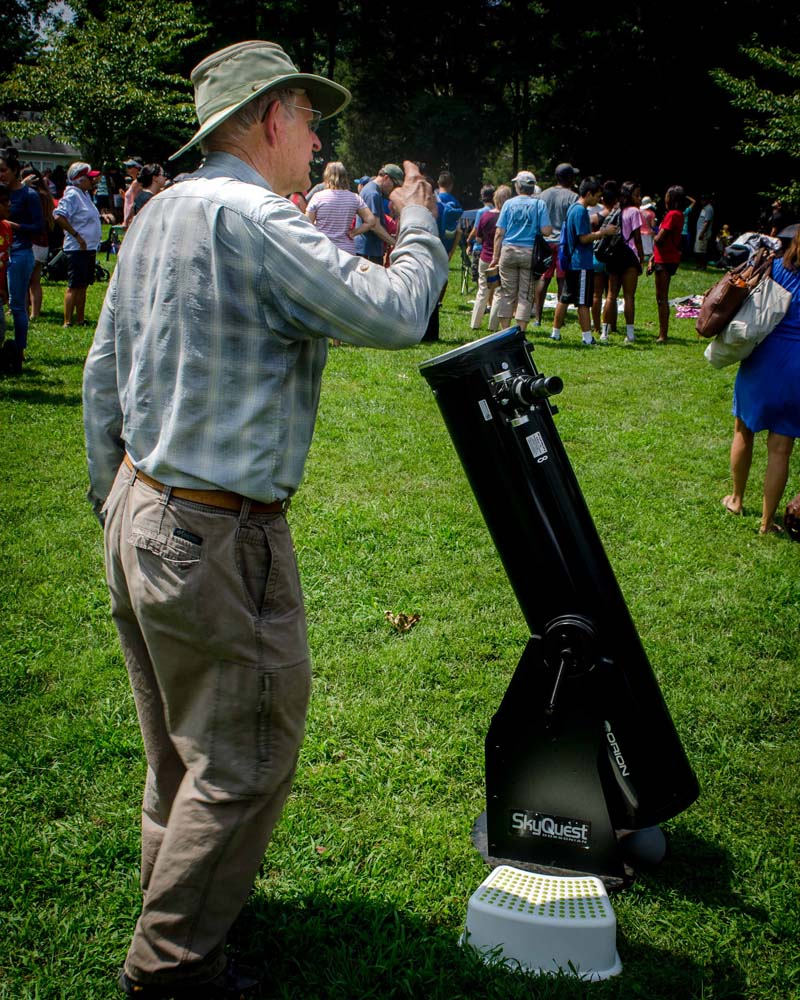 Man explaining use of telescope to view the eclipse