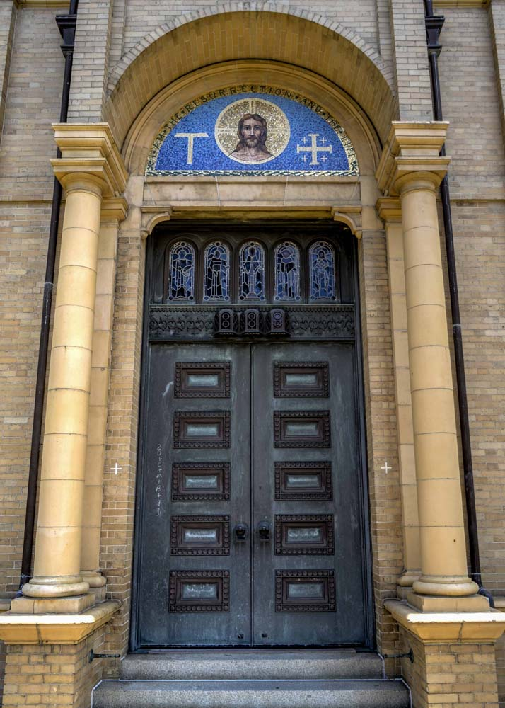 Western door to the church, with two styles of cross and image of Christ above the doors